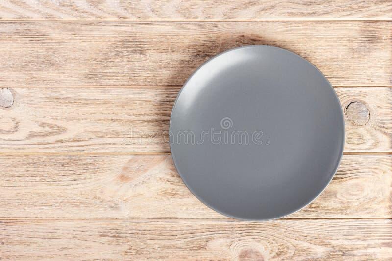 与拷贝空间灰色空的圆的板材的顶视图在木背景 库存图片
