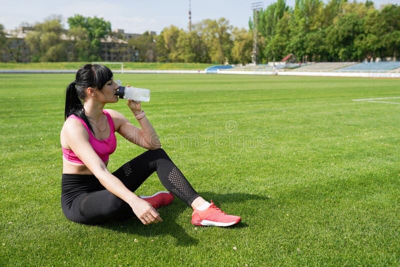与拷贝空间的体育背景 女子运动员在一热的天休假,她饮用水,在奔跑 r 免版税库存照片
