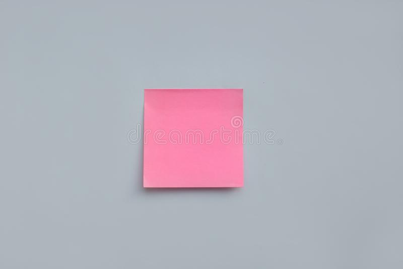与拷贝空间的桃红色贴纸笔记在蓝色背景 库存照片
