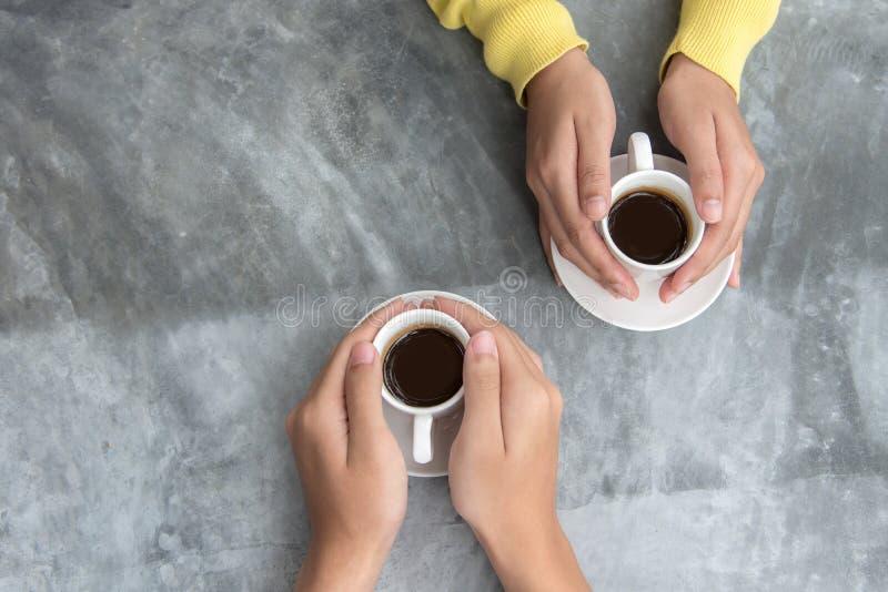 与拷贝空间的顶视图 在握充满咖啡爱的爱的夫妇手在桌上 免版税库存图片