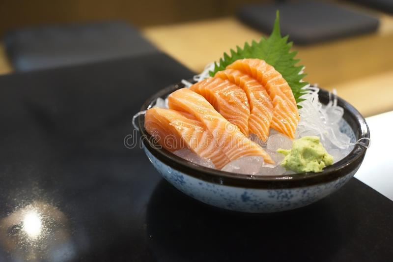 与拷贝空间,与山葵的未加工的三文鱼生鱼片的日本烹调在黑碗 库存照片