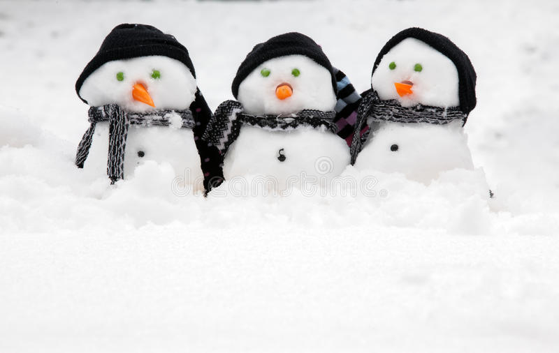 与拷贝空间的三个逗人喜爱的雪人 免版税库存图片