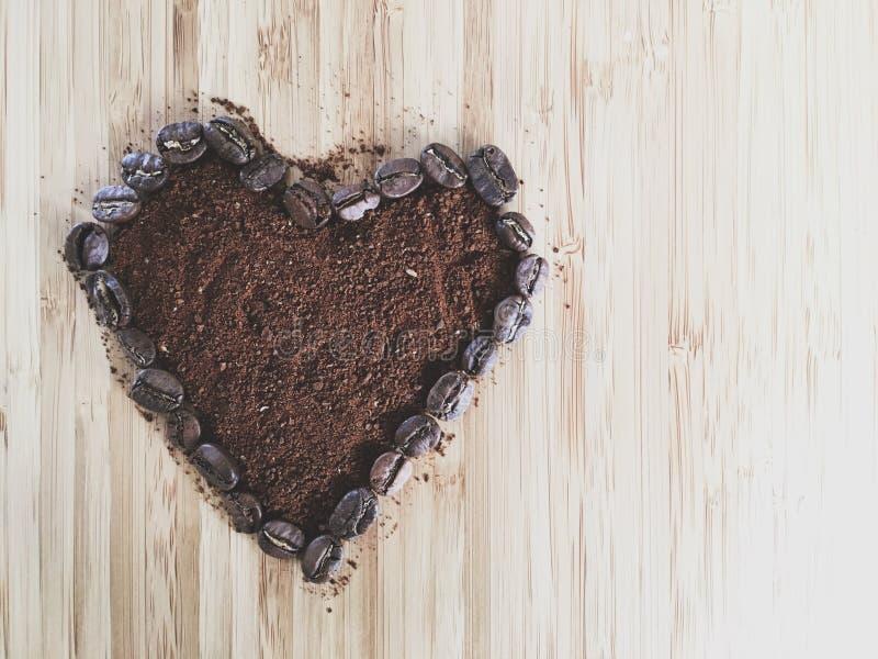 与拷贝空间的心脏形状咖啡豆和碾碎的咖啡 库存图片