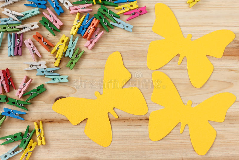 与拷贝空间的黄色纸板蝴蝶和在木背景的五颜六色的微型晒衣夹 免版税库存图片