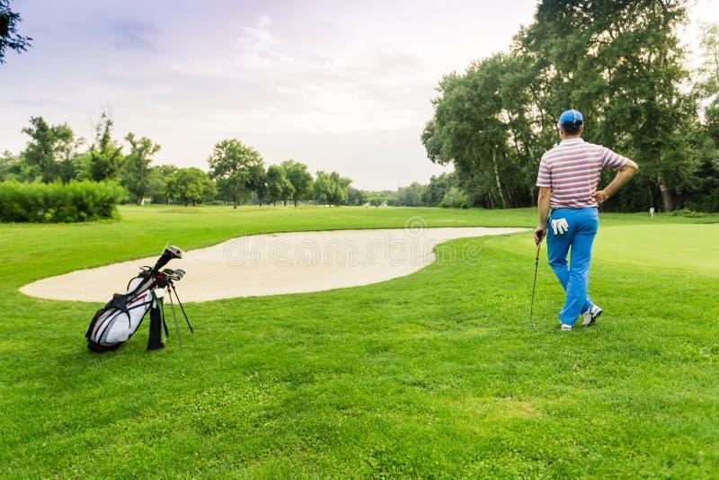 与拿着俱乐部的高尔夫球运动员的美好的打高尔夫球的风景 免版税库存照片