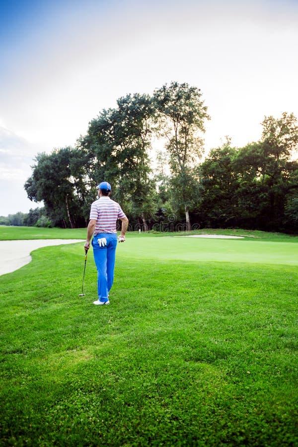 与拿着俱乐部的高尔夫球运动员的美好的打高尔夫球的风景 免版税库存图片