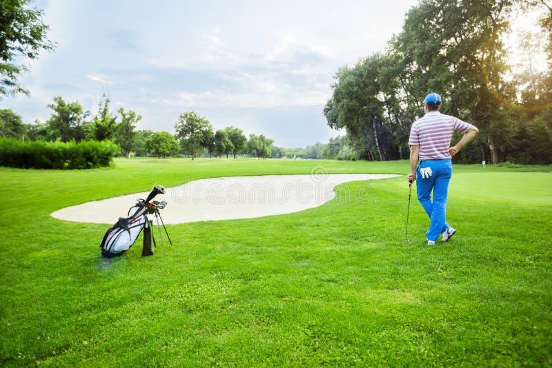 与拿着俱乐部的高尔夫球运动员的美好的打高尔夫球的风景 库存图片
