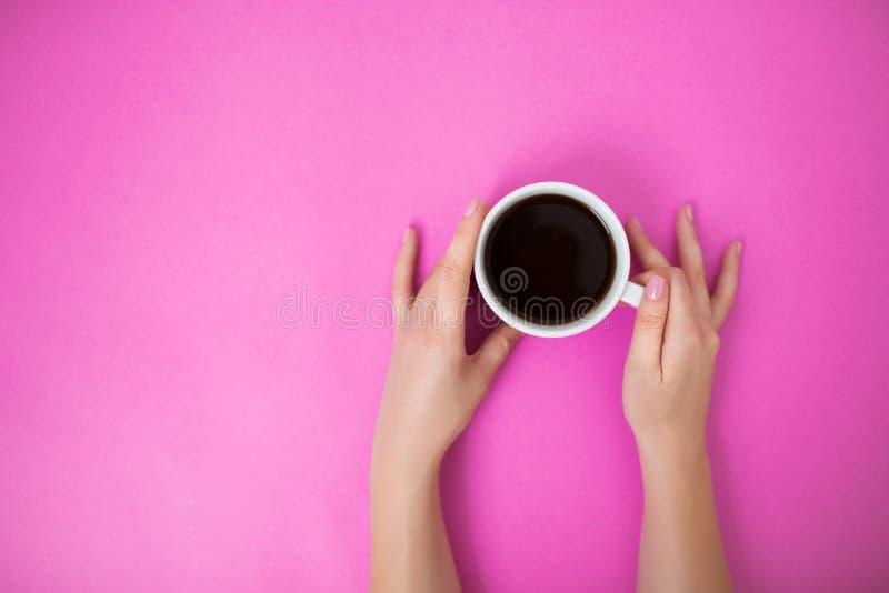 与拿着咖啡杯用两只手的妇女的Flatlay 图库摄影