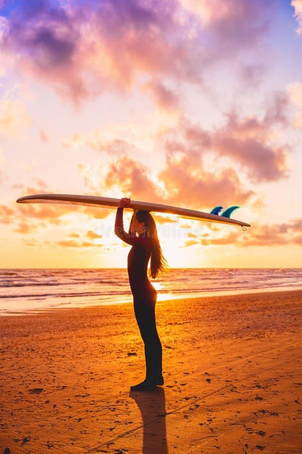 与拿着在海滩的冲浪者女孩的剪影冲浪板在温暖的日落或日出 冲浪者和海洋 库存照片