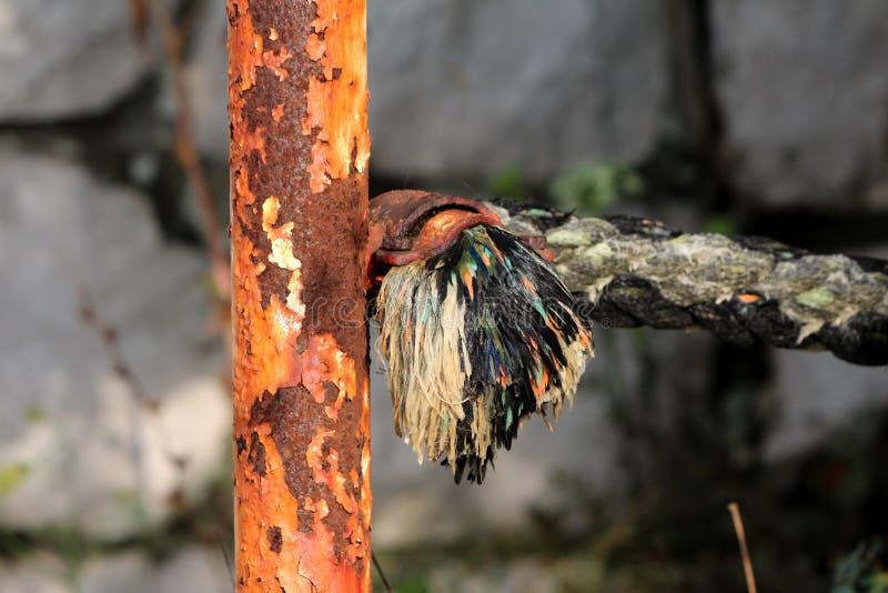 与拿着强的海军绳索服务的破裂的油漆的充分地生锈的金属杆作为有石墙的装饰篱芭在背景中 库存照片