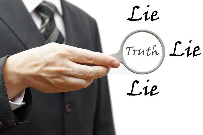与拿着放大镜的商人的真相和谎言概念 库存图片