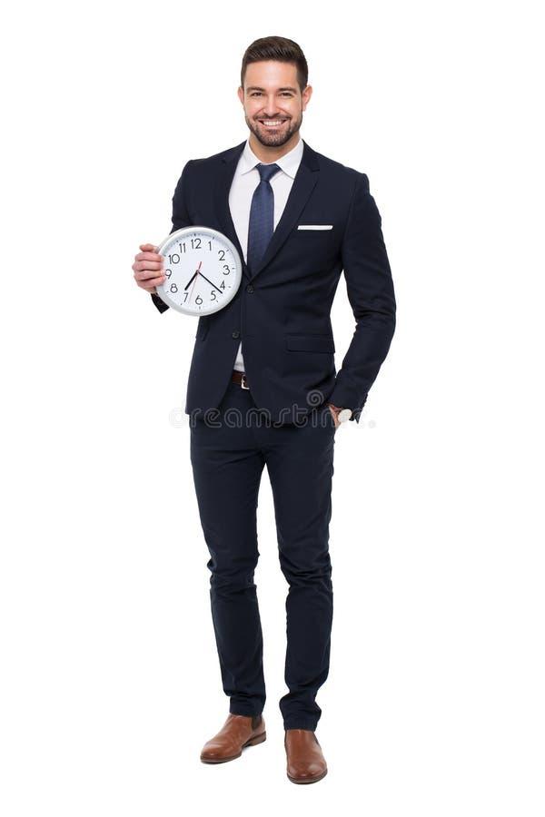 与拿着时钟isolat的牙微笑的年轻stylishg商人 库存图片
