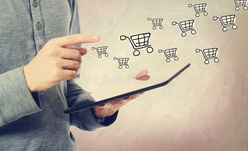 与拿着片剂的人的网上购物 库存照片