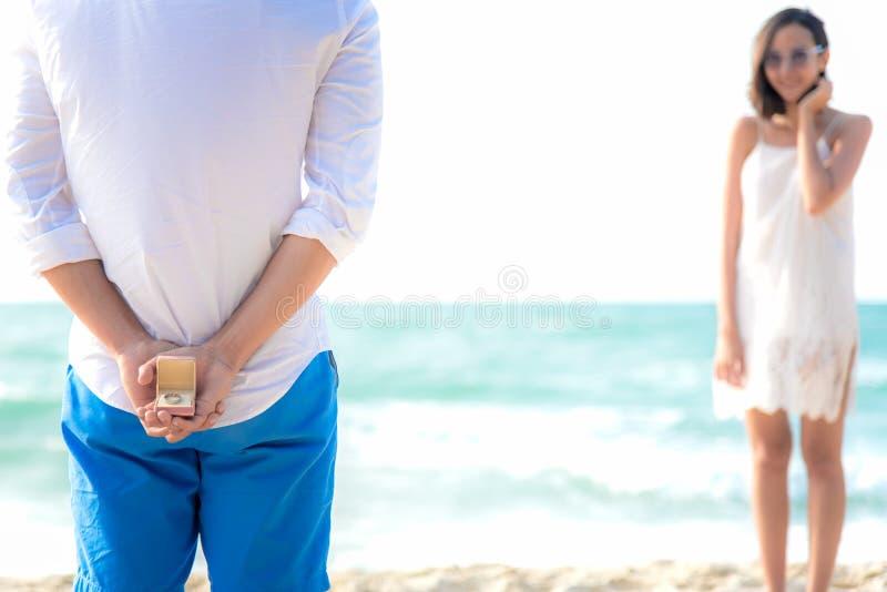 与拿着白色圆环的人的浪漫概念提出在海滩的结婚提议 在豪华reso的亚洲夫妇恋人蜜月 免版税库存图片