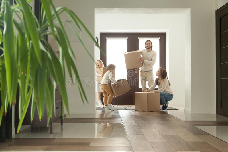与拿着箱子的孩子的愉快的家庭移动在新房里 免版税库存图片