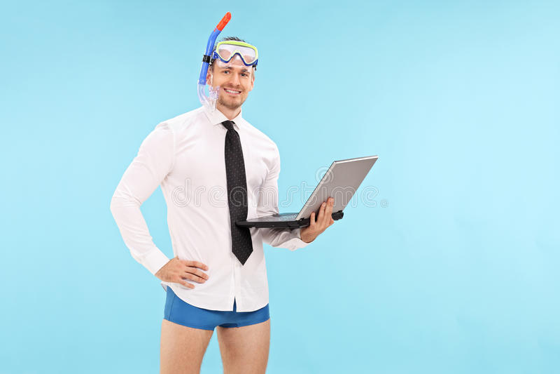 与拿着膝上型计算机的潜水面具的商人 免版税库存图片