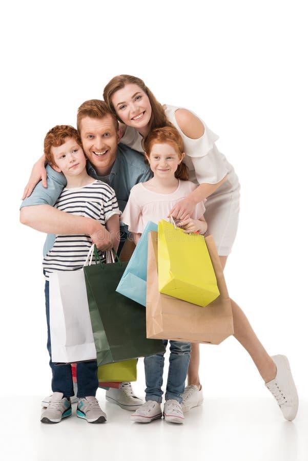 与拿着购物袋和微笑对照相机的两个孩子的愉快的红头发人家庭 库存照片