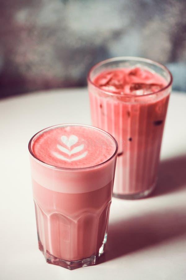 与拿铁艺术的两时髦甜菜根lattes在咖啡馆的桌上 图库摄影