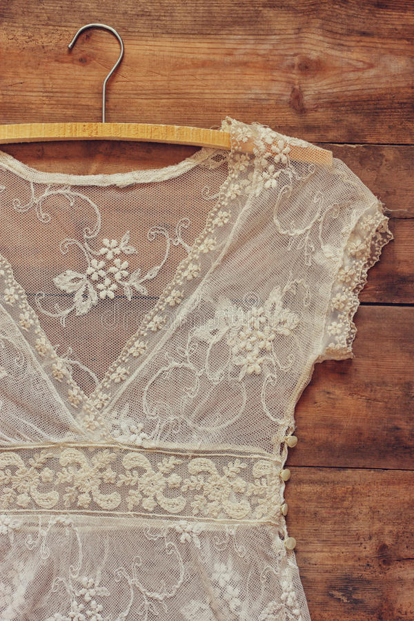 与挂衣架的葡萄酒白色钩针编织鞋带上面在木背景 免版税图库摄影