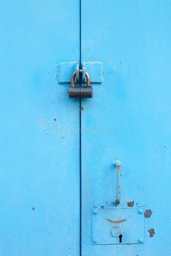 与挂锁的金属蓝色门 有匙孔的老车库门 免版税库存图片