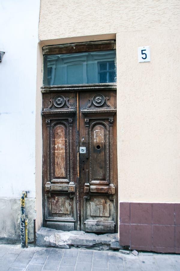 与挂锁窗口破碎石块步的古老木门 库存图片