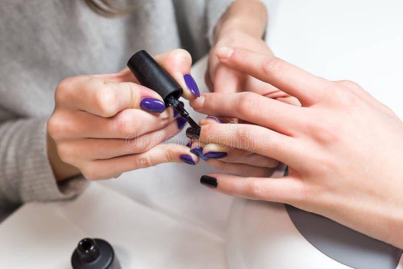 与指甲油的美好的修指甲过程 免版税库存照片