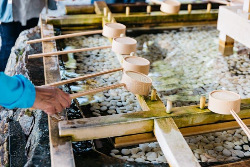 与挖出洗的游人的圣水寺庙他们的手水在去前祀奉在北海道寺庙 免版税图库摄影