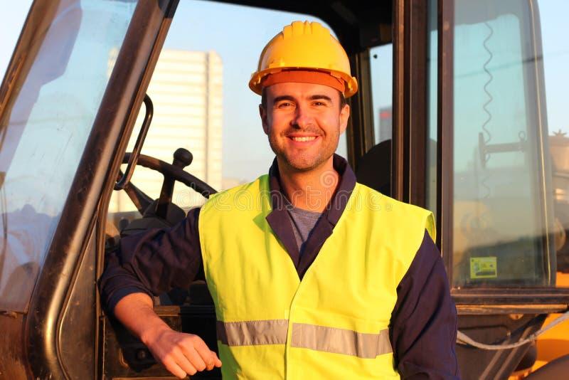 与挖掘机的建筑司机在背景 免版税图库摄影