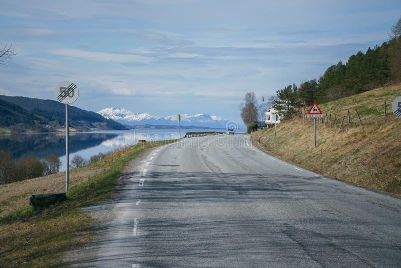 与挪威路的美好的风景在海湾,在背景的山附近 挪威春天 免版税库存图片