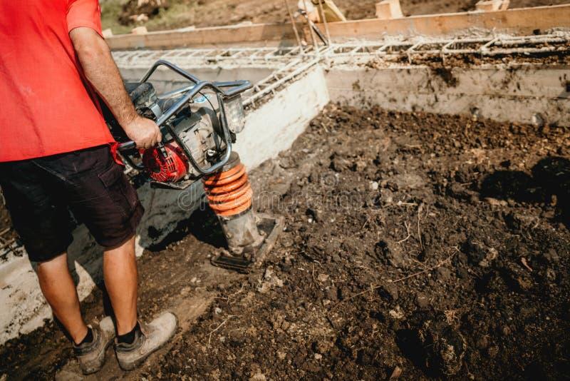与振动击实机器的工作者变紧密的土壤在基础时运作 免版税库存图片