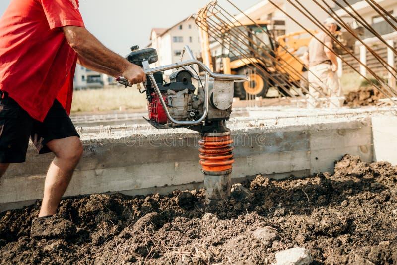 与振动击实机器的建筑工人变紧密的土壤 库存照片