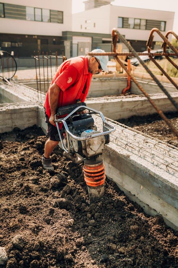 与振动击实机械的建筑工人变紧密的土壤 库存图片