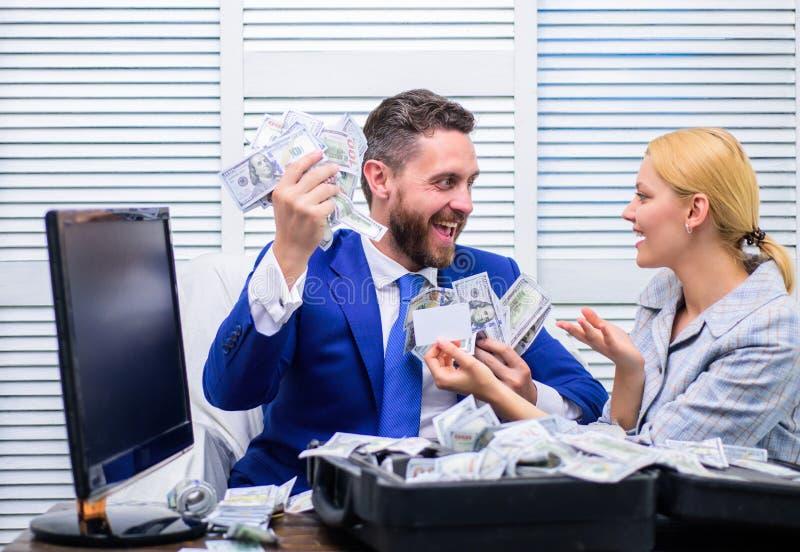 与捆绑的微笑的商人美国美元现金金钱在办公室 与美元金钱堆的愉快的商人在 免版税库存照片
