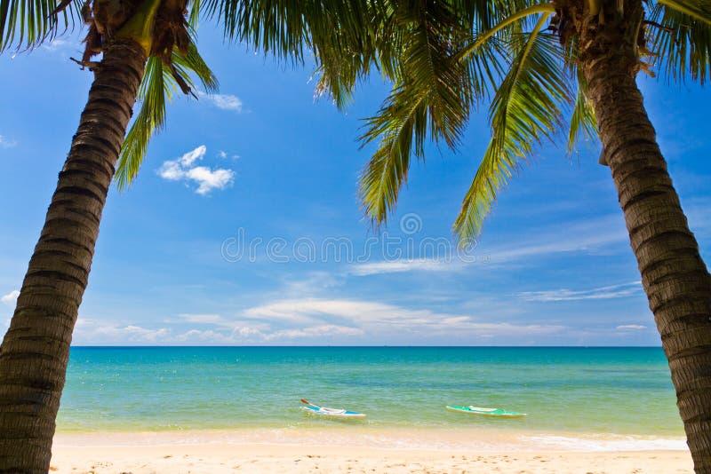 与掌上型计算机和独木舟的沙子海滩 库存照片