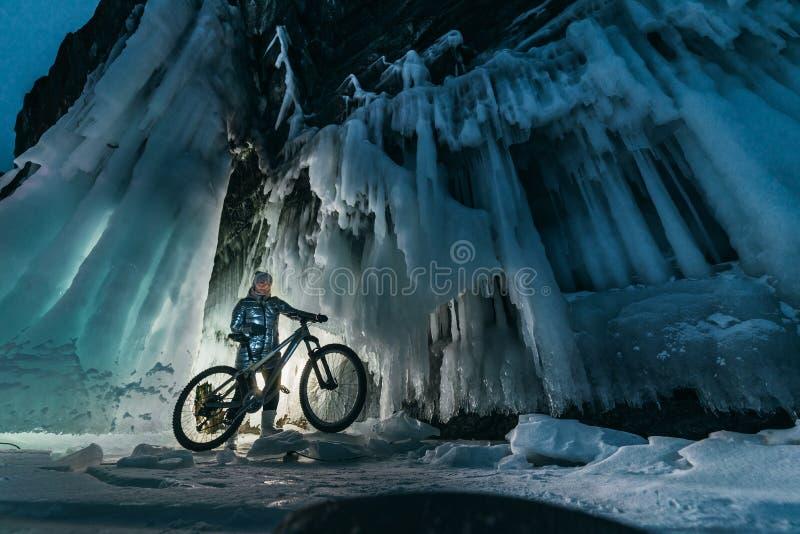 与探索神奇冰洞穴洞的妇女的超现实的风景 室外冒险自行车 探索巨大的冰冷的洞的女孩 库存图片