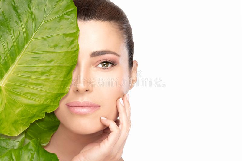 与接触她的在叶子后的一年轻美女的皮肤护理概念面孔 温泉秀丽画象 库存图片