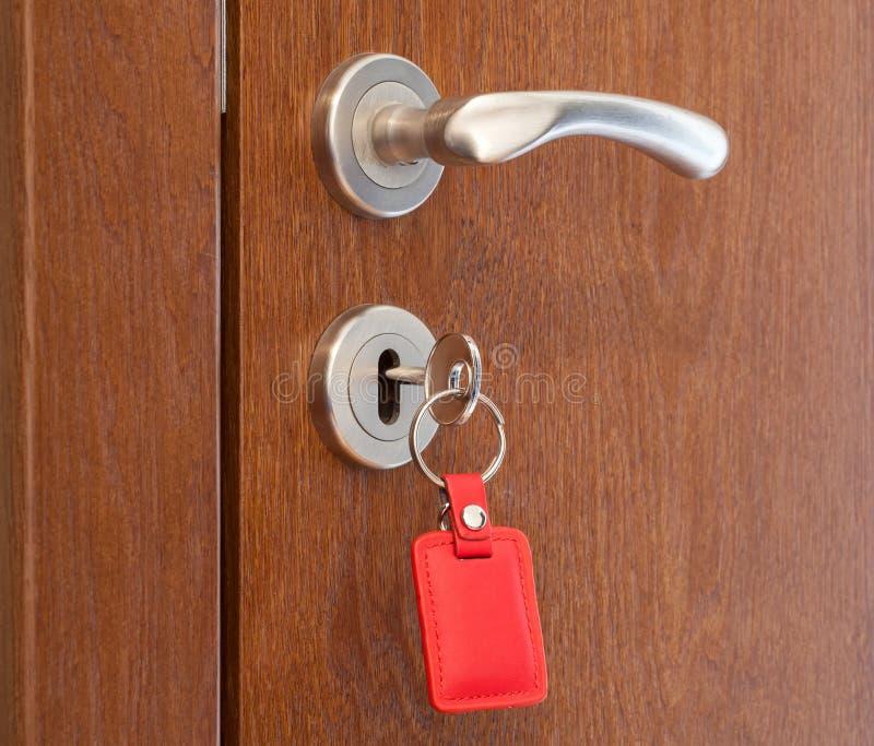 与插入键的门把手在与红色keyholder的匙孔 免版税图库摄影