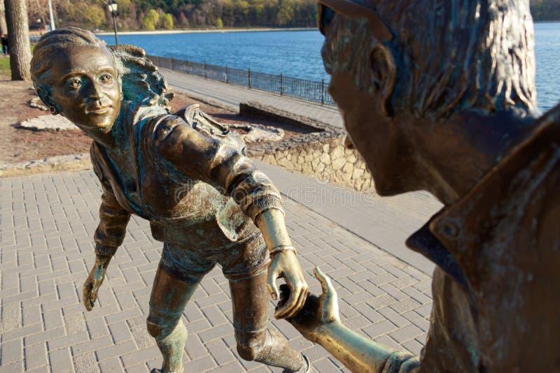与握她的手的男孩和女孩的雕象 免版税图库摄影
