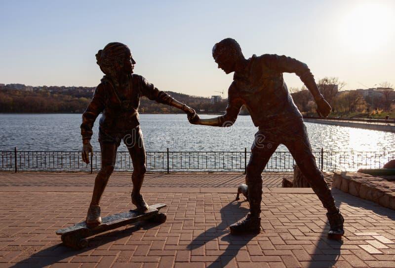 与握她的手的男孩和女孩的雕象 免版税库存图片