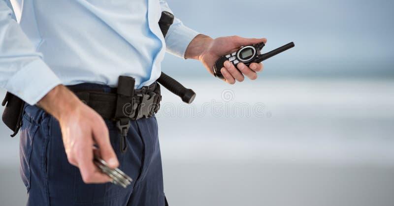 与携带无线电话和袖口的治安警卫 弄脏  免版税库存图片