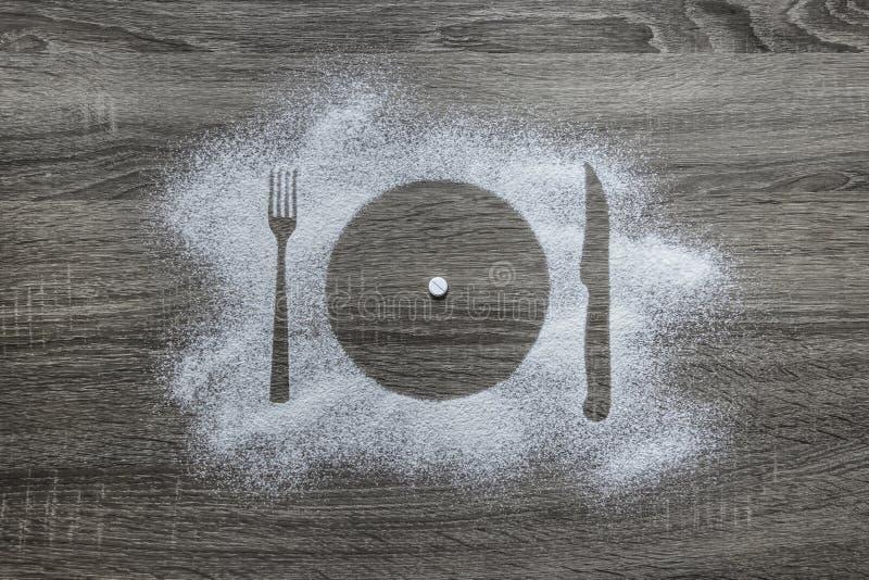 与搽粉的粉末的木背景积雪与剪影板材叉子刀子装置是一种白色圆的片剂 图库摄影