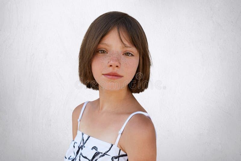 与摆在对白色混凝土墙的雀斑和短发的悦目深色的孩子在白色礼服穿戴了 小孩机智 免版税库存照片