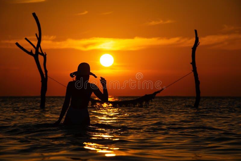 与摆在日落的,马尔代夫浪漫风景海的摇摆的美丽的年轻女人剪影 免版税图库摄影