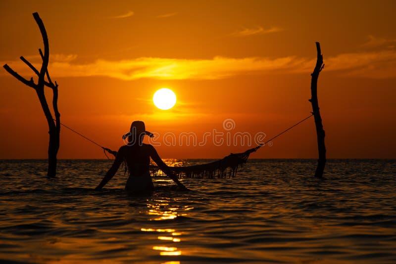 与摆在日落的,马尔代夫浪漫风景海的摇摆的美丽的年轻女人剪影 免版税库存照片