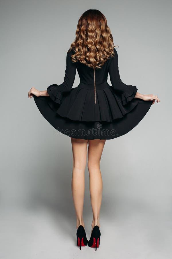 与摆在有被装饰衣裙的裙子和高跟鞋的美丽的黑礼服的波浪发的深色的模型 图库摄影