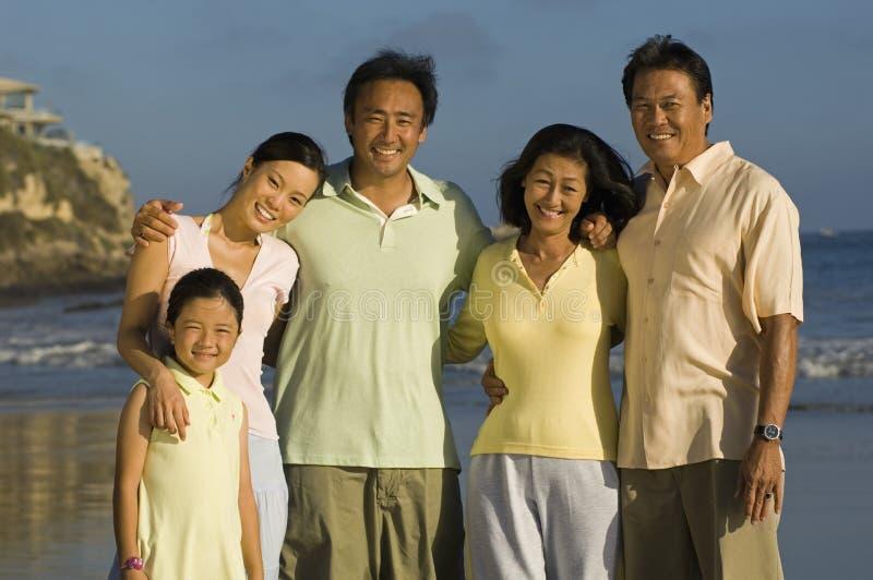 与摆在海滩的女孩的家庭 免版税库存照片