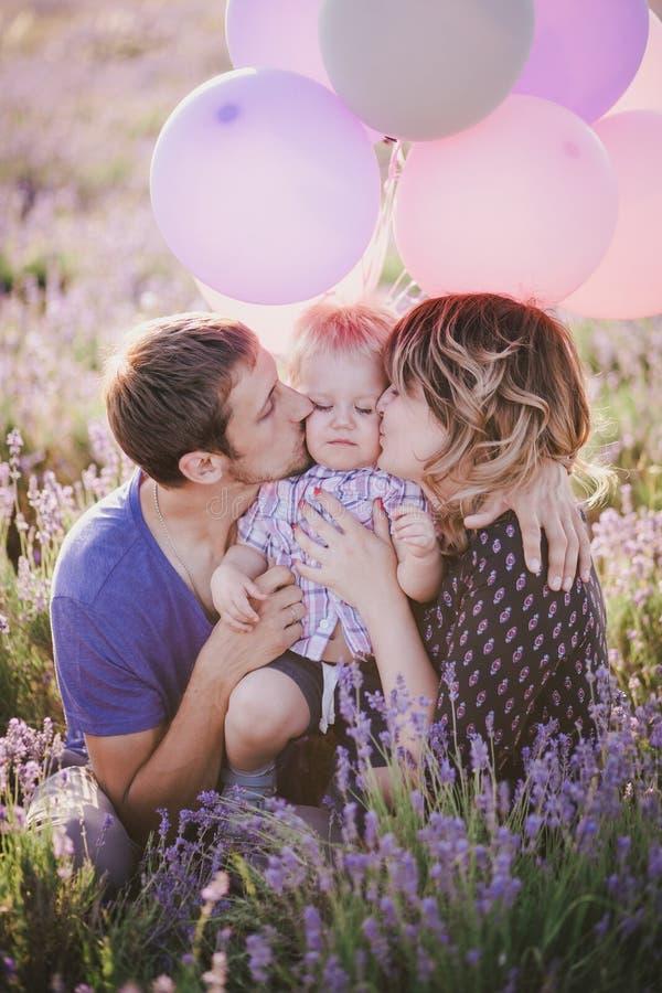与摆在淡紫色领域的五颜六色的气球的愉快的家庭 免版税图库摄影