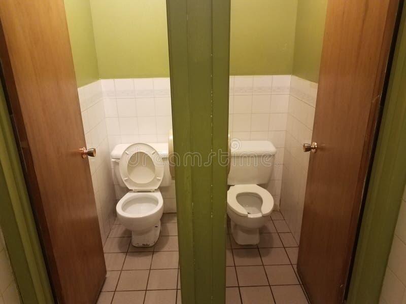与摊位的两间洗手间在绿色和白色卫生间里 库存图片