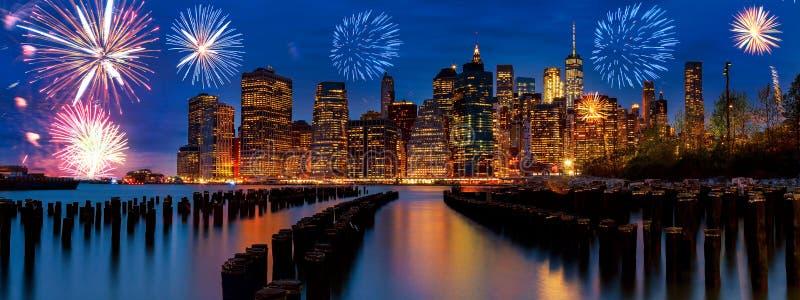 与摩天大楼的闪耀的庆祝烟花纽约曼哈顿地平线在哈得逊河阐明了光在黄昏afte 免版税库存图片