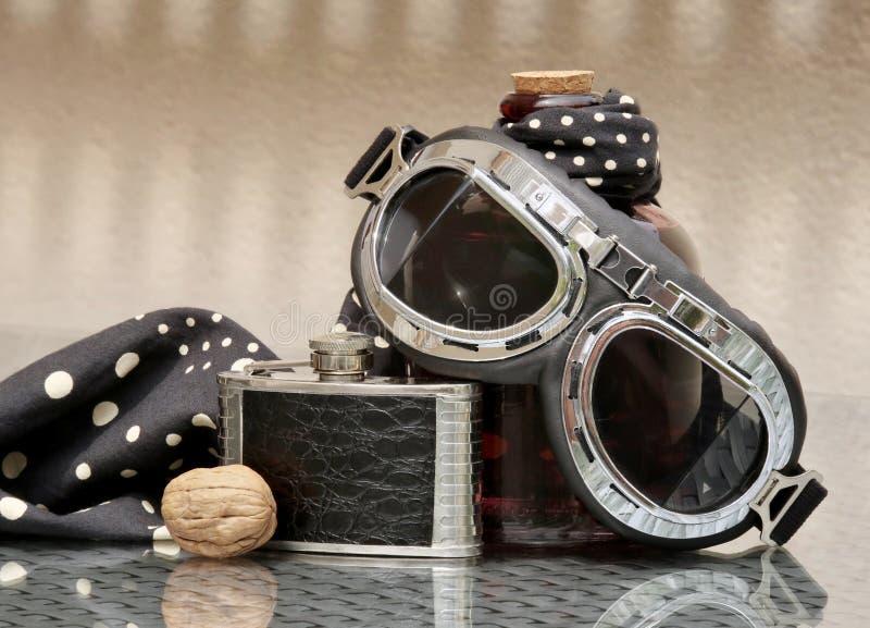 与摩托车风镜和熟悉内情的烧瓶的静物画 库存照片